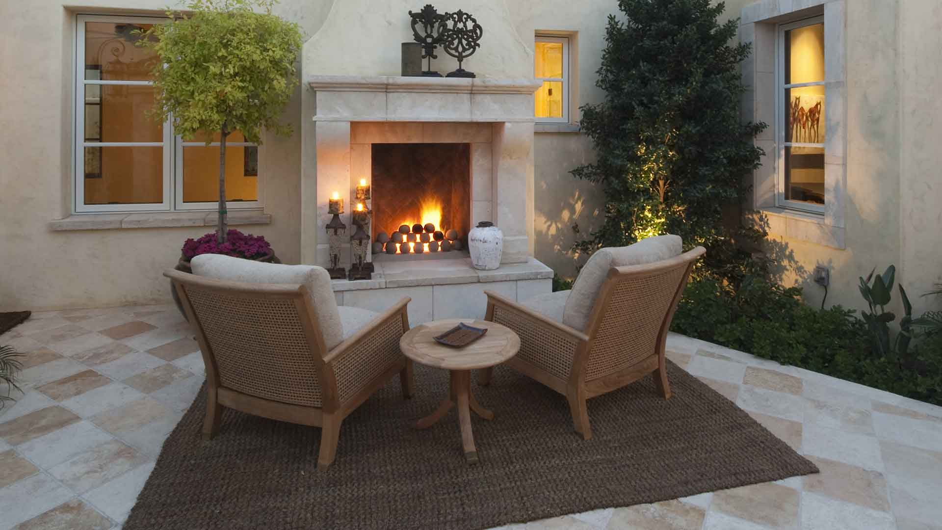 This custom outdoor fireplace adds entertainment space to this Manalapan, FL estate.