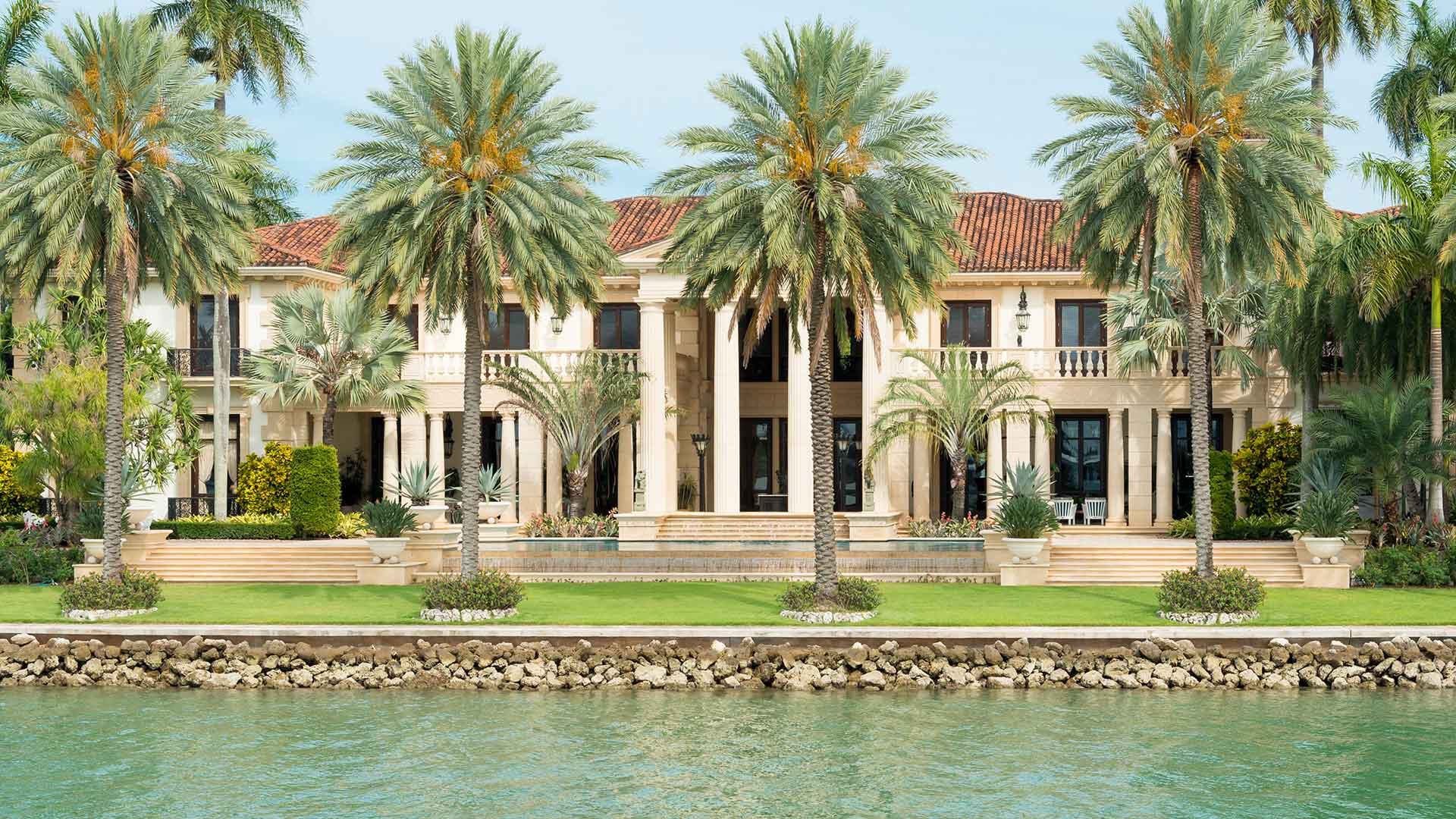This waterfront estate in Wellington, FL has well-manicured landscaping.